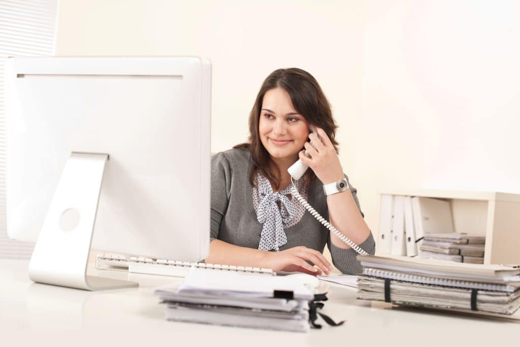 Sales professional using lead management software and is smiling.
